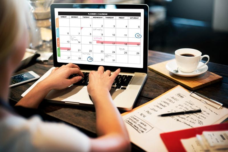 Frau am Laptop ruft ihren Kalender auf