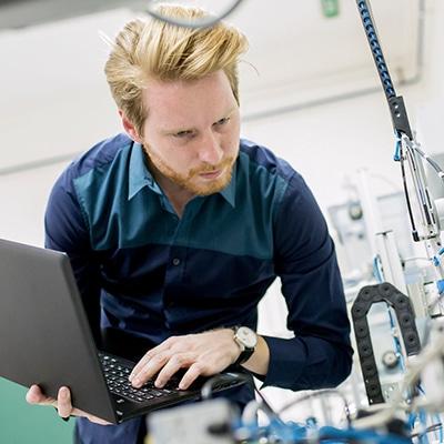 Cad-Fachkraft mit Laptop an einer Maschine