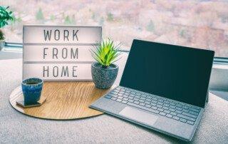"""Laptop mit Leuchttafel daneben mit der Aufschrift """"Work from Home"""""""