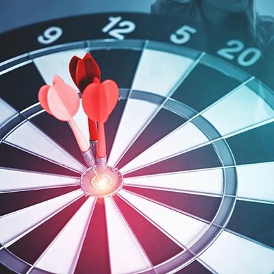 Zielscheibe mit drei roten Pfeilen in der Mitte steckend. Iin Blau gehalten