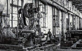 Bild einer alten Pumpenanlage vor einem Fachwerkhaus