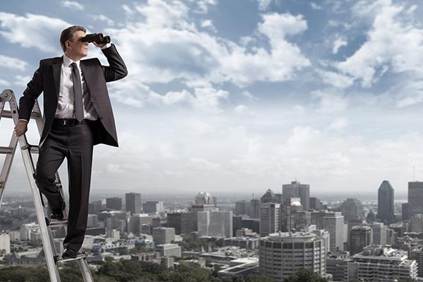 Mann mit Fernglas auf einer Leiter, im Hintergrund die Skyline einer Großstadt