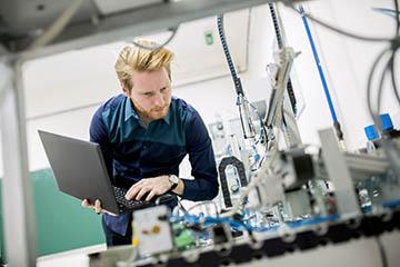 Mann mit Laptop in der Hand mit Blick auf eine Maschine