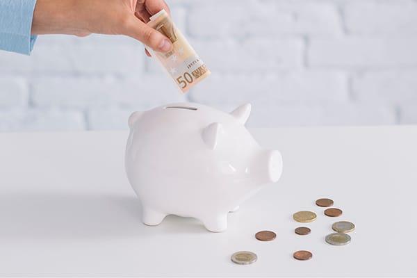 Hand einer Frau steckt einen Fünfzigeuroschein in ein Sparschwein drumherum liegen ein paar Münzen